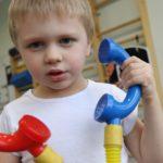 Chłopiec bawiący się słuchawkami telefonu.