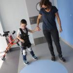 Uczeń wraz z fizjoteraputką podczas ćwiczeń chodu z wykorzystaniem kominezonu Dunag.
