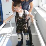 Uczeń w kominezonie Dunag podczas ćwiczeń z fizjoteraputą na poręczach asekuracyjnych.