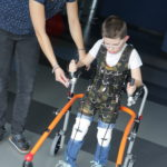 Uczeń wraz z fizjoteraputką podczas ćwiczeń chodu z wykorzystaniem kominezonu Dunag oraz czterokołowego chodzika.