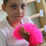 Uczeń bawiący się zabawką sensoryczną.