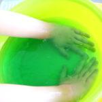 Dłonie zanurzone w misce wypełnionej substancją galaretowatą.