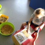 Dziewczynka wskazująca na etykietach materiały sypkie.