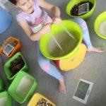 Dziewczynka bawiąca się materiałami sypkimi.