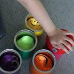 Dłoń podzcas wkładania miękkich piłeczek do kolorowych puszek.