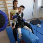 Podopieczny wraz z fizjoterapeutką podczas ćwiczeń w kominezonie Dunag na sprzęcie podwieszanym.