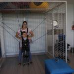 Podopieczny wraz z fizjoterapeutką podczas ćwiczeń w kominezonie Dunag w UGUL-u.
