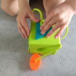Dłonie manipulujące zabawką dopasowując kształt do otworu.