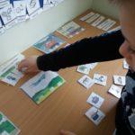 Uczeń podczas zajęć logopedycznych z zakresu budowania zdań.