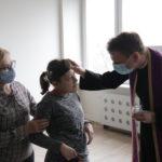 Ksiądz, w asyście wychowawcy, posypujący głowę popiołem uczennicy