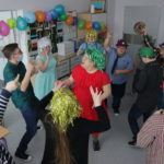 Starsi uczniowie tańczący podczas dyskoteki.