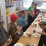 Starsi uczniowie siedzący przy stole podczas poczęstunku w tłusty czwartek..