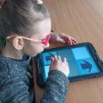 Uczennica wykonuąza zadanie z zakresu komunikacji z wykorzystaniem tabletu.