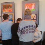 """Grupa uczniów obserwująca prezentowane w fotoramach prace plastyczne podczas wystawy """"Jesienne wspomnienia""""."""