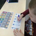 Chłopiec podczas ćwiczenia grafomotoryczno -logopedycznego.
