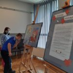 """Uczniowei obserwujący fotoramy prezetujące prace plastyczne podczas wystawy """"Jesienne wspomnienia""""."""