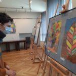 Uczeń zwiedający wystawę prac plastycznych.