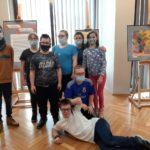 """Zdjęcie grupy uczniów na tle wystawy prac plastycznych podczas wystawy """"Jesienne oblicza""""."""