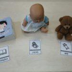 Symbole MAKATON oraz ich rzeczowe odpowiedniki: książka, lalka, miś.