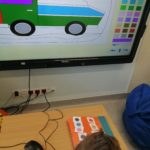 """Uczeń wykonujący zadanie związane z kolorami na tablicy interaktywnej z wykorzystaniem przycisku """"Big switch""""."""