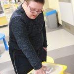 Uczeń podczas ćwiczenia manulanego z wykorzystaniem skarpet.