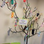 Dekoracja w postaci drzewa z przyczepionymi kolorowymi skarpetami nie do pary oraz napis Światowy Dzień Zespołu Downa.