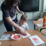 Chłopiec odbijający dłoń na kartce z pomocą wychowawcy.