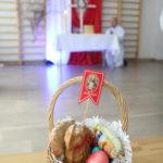 Koszyczek ze święconką na tle dekoracji ołtarza.