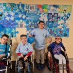 Grupa uczniów ubrana w niebieskie barwy pozująca na tle obrazu stworzonego z niebieskich puzzzli.
