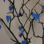 Wizerunak fragmenty drzewwa - gałęzi przyozdobionych niebieskimi, papierowymi sercami.