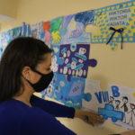 Nauczycielka podczas przyklejania fragmentu obrazu z niebieskich puzzli.