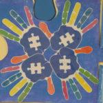"""Jeden z """"niebieskich puzzli"""" - 4 kolorowe dłonie z wizerunkiem puzzli."""