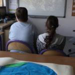 Uczniowie oglądający prezentajcę multimedialną z okazji Dnia Ziemii.