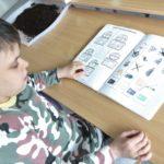 Uczennica podczas stolikowej pracy dydaktycznej o tematyce nawiązującej do Dnia Ziemi.