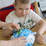 """Uczeń podczas wykonywania przestrzennej pracy plastycznej """"planeta ziemia""""."""