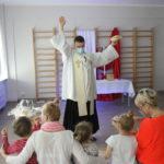Ksiądz podczas błogosławieństwa wielkanocnych pokarmnów prezentujący przedszkolakom chleb.