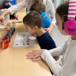 Przedszkolaki podczas farbowania jajek wielkanocnych.