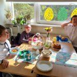 Uczniowei zasiadający przy stole do wielkanocnego śniadania.