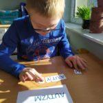 """Uczeń ukaldający słowo """"auztyzm"""" z rozsypanki literowej."""