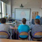 """Grupa uczniów podczas oglądania prezentacji multimedialnej """"Oswajamy autyzm""""."""