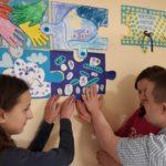 Grupa uczniów podczas przyklejania fragmentu obrazu z niebieskich puzzli.