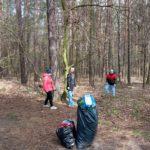 Uczniowie w lesie podczas zajęć z zakresu dbania o czystość śrdowiska.