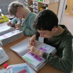 Uczniowie wykonujący zadanie w zeszytach uczniowskich związane z majowymi świetami narodowymi.