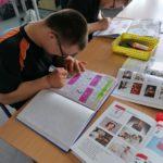 Uczniowie wykonujący zadanie w zeszytach uczniowiskich związane z majowymi świetami narodowymi.