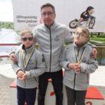 Zawodnicy z medalami w asyście trenera.