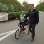 Zawodnik na rowerze ytrójkołowym w asyście trenera.