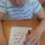 Uczeń podczas zadania dydaktycznego z zakresu liczenia z wykorzystaniem karty pracy.