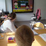 Uczniowei obserwujący patriotyczna prezentacją na tablicy multimedialnej.