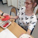 Uczennica robiąca biało - czerwone odbitki dłoni na papierze.