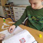 Uczeń wyklejający w zeszycie wiersz zilustrowany symbolami Makaton.